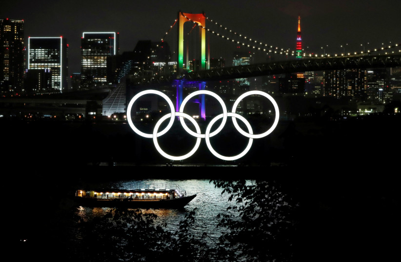 The Rainbow Bridge and Tokyo Tower are illuminated with Olympic colours to mark 100 days countdown to the Tokyo 2020 Olympics that have been postponed to 2021 due to the coronavirus disease (COVID-19) outbreak, in Tokyo, Japan April 14, 2021 (photo credit: REUTERS/ISSEI KATO)