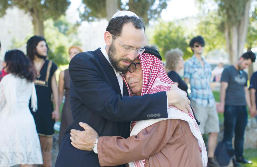 RABBI YAKOV NAGEN of Otniel embraces Haj Ibrahim Ahmad Abu el-Hawa of Jerusalem during an event called The Big Hug, in 2013. (photo credit: SARAH SCHUMAN/ FLASH90)