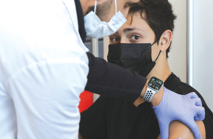 A TEENAGER receives a vaccination against COVID-19 in Tel Aviv, earlier this year. (photo credit: RONEN ZVULUN/REUTERS)