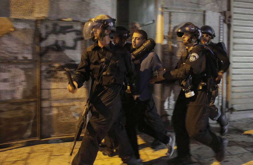 Israeli police officers detain a Palestinian suspected of throwing stones during clashes outside Jerusalem's Old City (photo credit: AMMAR AWAD/REUTERS)