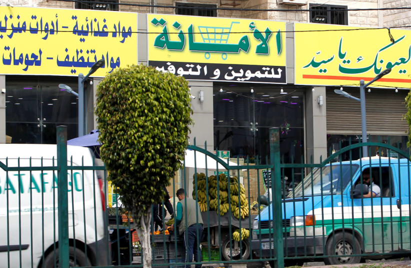 A view shows a market for groceries with a Hezbollah slogan on it, in Beirut suburbs, Lebanon April 16, 2021. (photo credit: REUTERS/STRINGER)