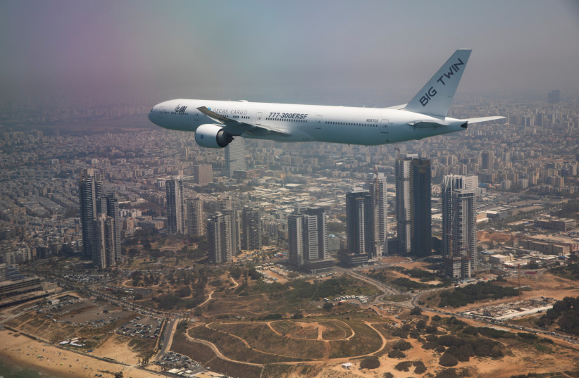 An IAI cargo Boeing 777 flies over Tel Aviv during a flyover by IAI (Israel Aerospace Industries) planes on Israel's Independence Day, which marks the 73rd anniversary of the creation of the state, Israel April 15, 2021. (photo credit: AMIR COHEN/REUTERS)