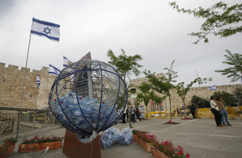 """A large ball depicting the earth is filled with empty water bottles at an environmental happening held by the Old City of Jerusalem on """"Save Earth Day'. April 23, 2009.  (photo credit: MIRIAM ALSTER/FLASH90)"""