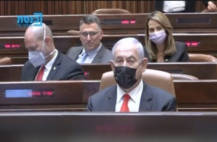 A screenshot shows New Hope leader Gideon Sa'ar winking behind Prime Minister Benjamin Netanyahu in the Knesset on April 19, 2021. (photo credit: SCREENSHOT/KNESSET CHANNEL)