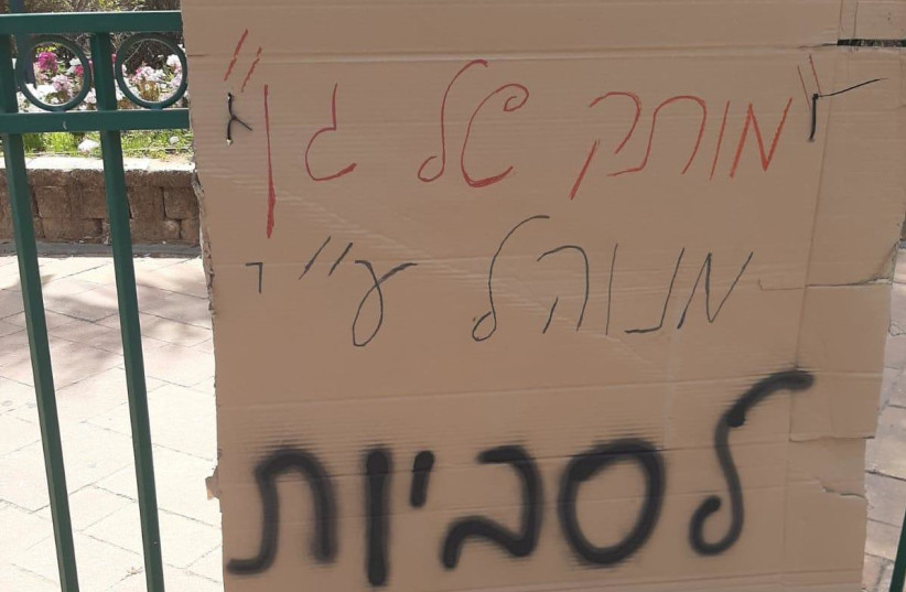 """A sign which says """"[this kindergarten] is run by lesbians"""" was hung on a short railing near Moatza square in Be'er Ya'acov, April 21, 2021. (photo credit: THE AGUDAH - ISRAEL'S LGBT TASK FORCE)"""
