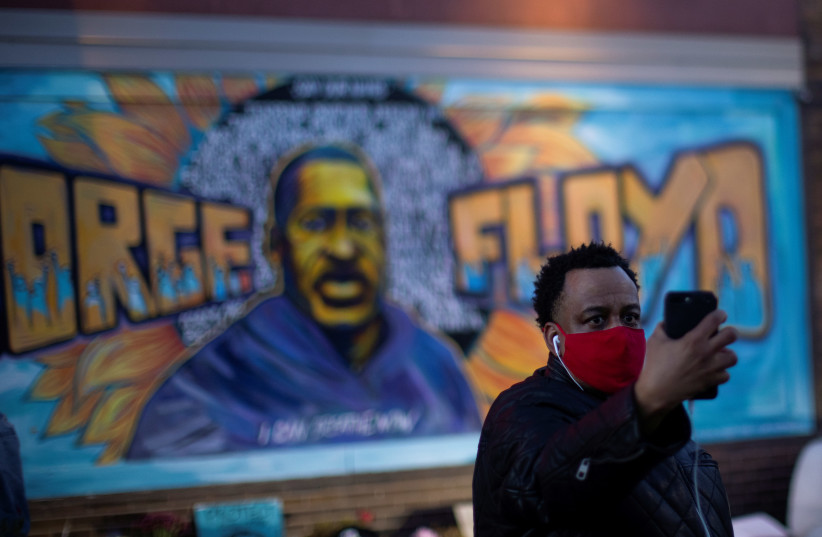 A local resident takes a selfie in front of a mural of George Floyd after the verdict in the trial of former Minneapolis police officer Derek Chauvin, found guilty of the death of George Floyd, at George Floyd Square in Minneapolis, Minnesota, US, April 20, 2021. (photo credit: REUTERS/CARLOS BARRIA)