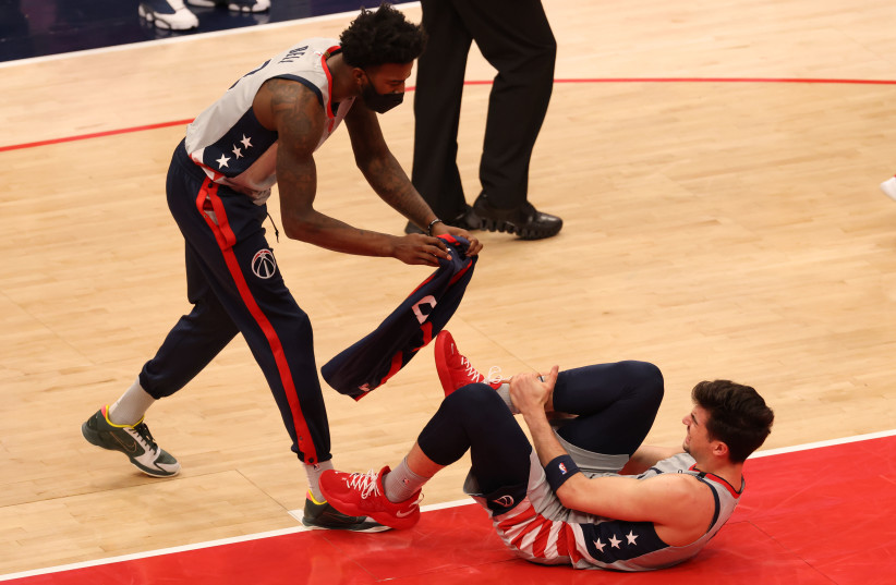 Apr 21, 2021; Washington, District of Columbia, USA; Washington Wizards forward Deni Avdija (9) is assisted by Wizards center Jordan Bell (7) after being injured against the Golden State Warriors in the second quarter at Capital One Arena. (photo credit: GEOFF BURKE-USA TODAY SPORTS/VIA REUTERS)