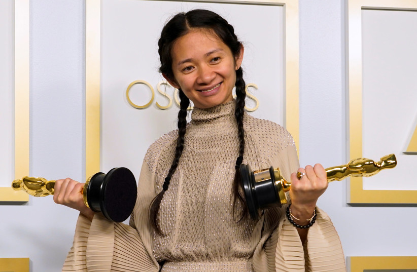 """Chloe Zhao, winner of the award for Best Picture for """"Nomadland,"""" poses in the press room at the Oscars, in Los Angeles, California, U.S., April 25, 2021.  (photo credit: REUTERS)"""