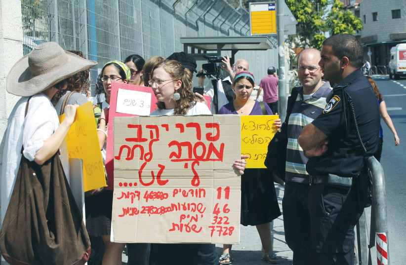 A WOMAN (foreground) holds a sign that says her husband has refused to give her a 'get' (writ of divorce) for nearly a year, at a protest outside the Justice Ministry in Jerusalem in 2011. (photo credit: YOSSI ZAMIR/FLASH90)