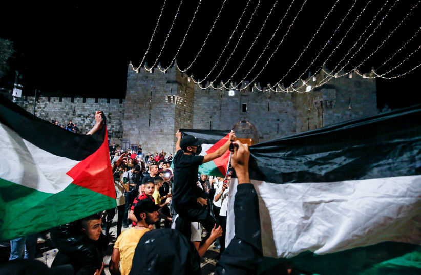 Arabs wave Palestinians flags at Damascus Gate in Jerusalem's Old City, during the holy Muslim month of Ramadan, April 25, 2021.  (photo credit: JAMAL AWAD/FLASH90)