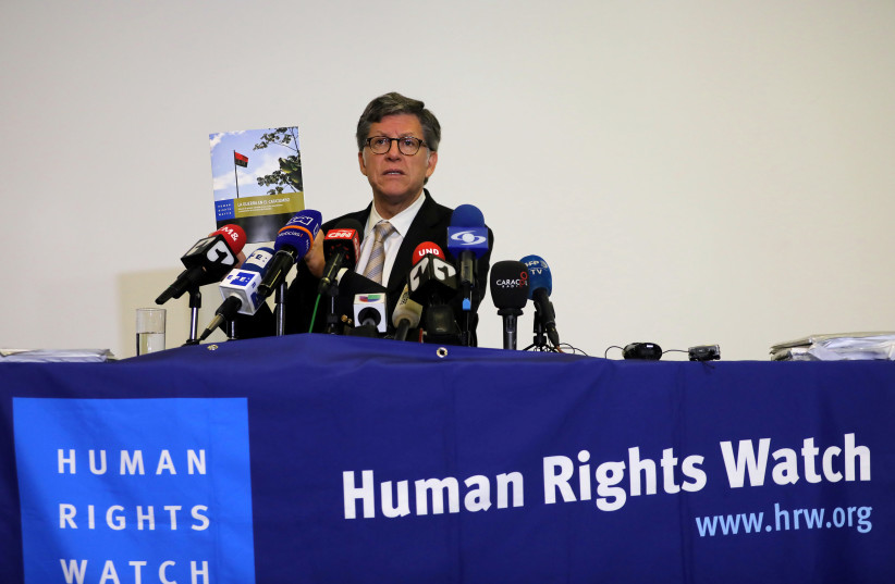 Jose Miguel Vivanco, director of Human Rights Watch Americas, holds up a report while addressing the media in Bogota (photo credit: REUTERS)