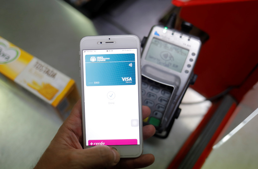 A shopper uses the mobile payment service Apple Pay at a supermarket, amid the coronavirus disease (COVID-19) outbreak, in Ronda, southern Spain October 9, 2020 (photo credit: REUTERS/JON NAZCA)