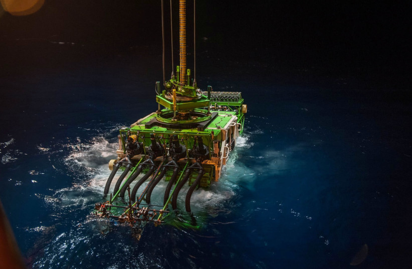 Patania II, a 25-tonne seabed mining robot, is lowered into the Pacific Ocean to begin a descent to the sea floor, in the Clarion Clipperton Zone of the Pacific Ocean, April 2021.  (photo credit: GSR/HANDOUT VIA REUTERS)