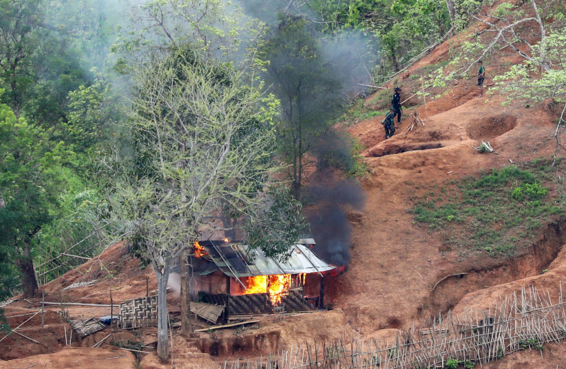 Ethnic minority Karen troops are seen after setting fire to a building inside a Myanmar army outpost near the Thai border, which is seen from the Thai side on the Thanlwin, also known as Salween, riverbank in Mae Hong Son province, Thailand, April 28, 2021. (photo credit: REUTERS/ATHIT PERAWONGMETHA)