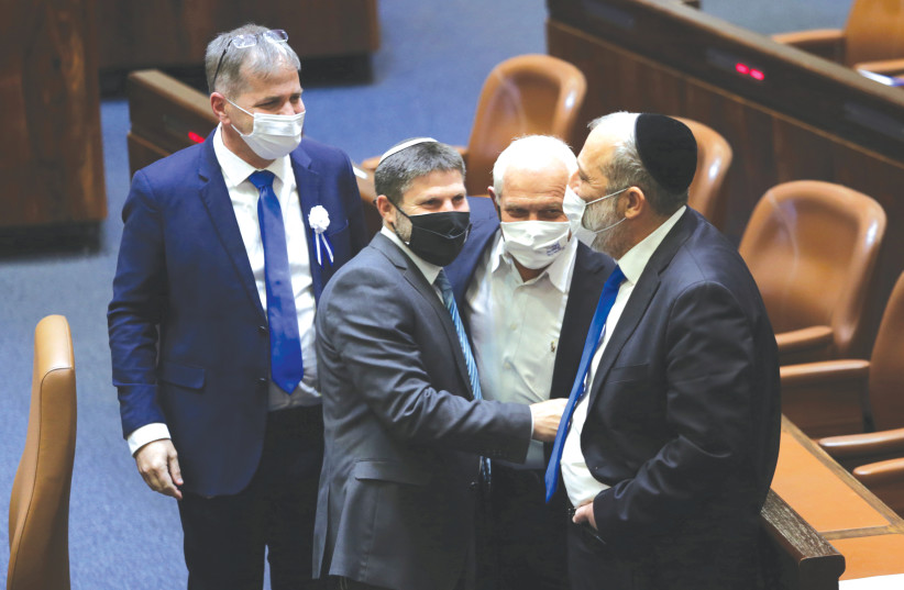 RELIGIOUS ZIONIST Party leader Bezalel Smotrich and Shas Party head Arye Deri shake hands at the Knesset swearing-in ceremony in Jerusalem on April 6. (photo credit: ALEX KOLOMOISKY/REUTERS)