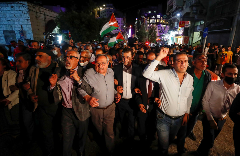 Palestinians take part in a rally demanding President Mahmoud Abbas to hold elections on planned time, in Ramallah in the Israeli-occupied West Bank April 29, 2021 (photo credit: REUTERS/MOHAMAD TOROKMAN)