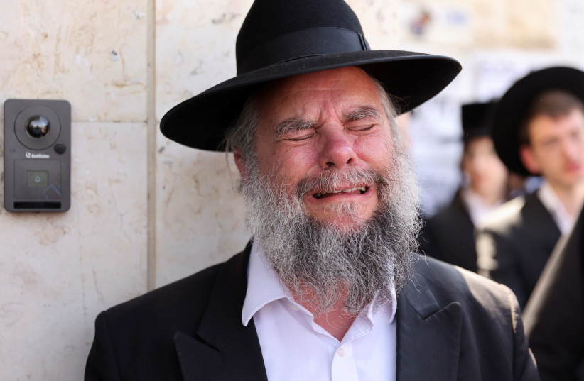 Ultra-Orthodox Jewish man reacts as he takes part in a funeral for Rabbi Elazar Goldberg after he died during Lag B'Omer commemorations, in Jerusalem on April 30, 2021 (photo credit: REUTERS/RONEN ZEVULUN)