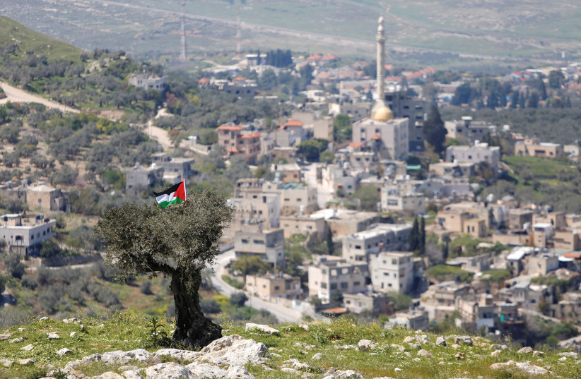 A PALESTINIAN flag hangs on a tree during a protest against settlements in An-Naqura near Nabulus. (photo credit: RANEEN SAWAFTA/ REUTERS)