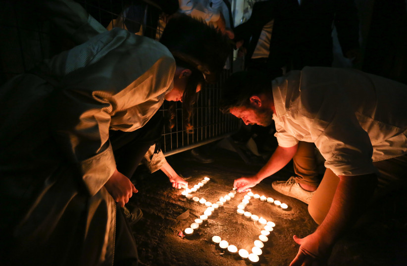 Ultra-orthodox Jews light candles for the 45 victims who were killed in a stampede, at the scene of the fatal disaster, at Mt Meron. May 01, 2021. (photo credit: DAVID COHEN/FLASH 90)