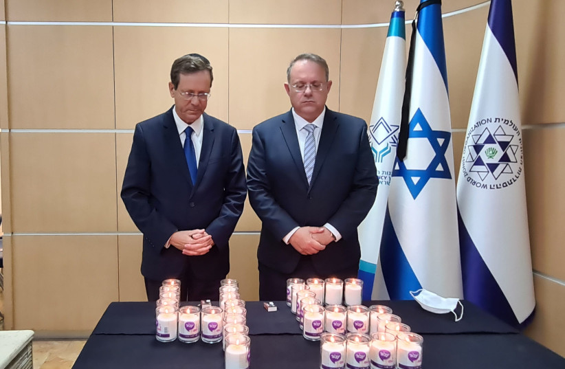Jewish Agency Chairman Isaac Herzog (left) and Acting director of the WZO Yaakov Haguel (right) light memorial candles for the victims of the Mount Meron tragedy, Sunday, May 2, 2021. (photo credit: THE JEWISH AGENCY)