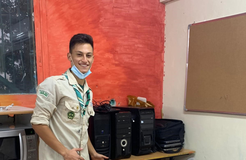 A Scout displays computers collecting for Mitchashvim (photo credit: Courtesy)