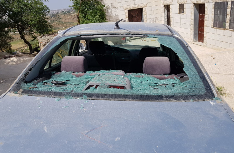 A car is seen smashed by stones in the Palestinian village of Jalud in the West Bank. (photo credit: YESH DIN)