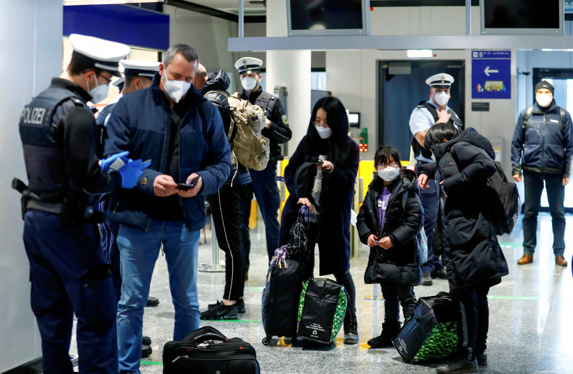 Federal police officers check air passengers arriving from Britain at Frankfurt Airport, as the spread of the coronavirus disease (COVID-19) continues, in Frankfurt, Germany, January 30, 2021.  (photo credit: REUTERS/RALPH ORLOWSKI)