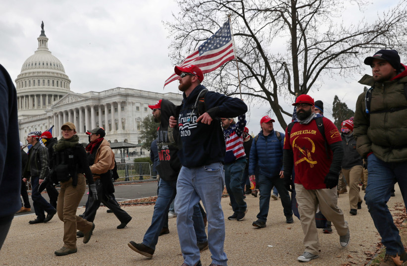 Members of the Proud Boys and supporters of US President Donald Trump show up at the US Capitol Building over an hour before supporters began to storm the building in Washington, US, January 6, 2021. (photo credit: REUTERS/LEAH MILLIS)