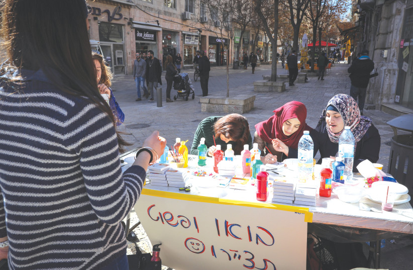 Muslim young women participate in a project by Bezalel art students inviting people on the street to draw themselves, in central Jerusalem, in 2017. (photo credit: NATI SHOHAT/FLASH90)