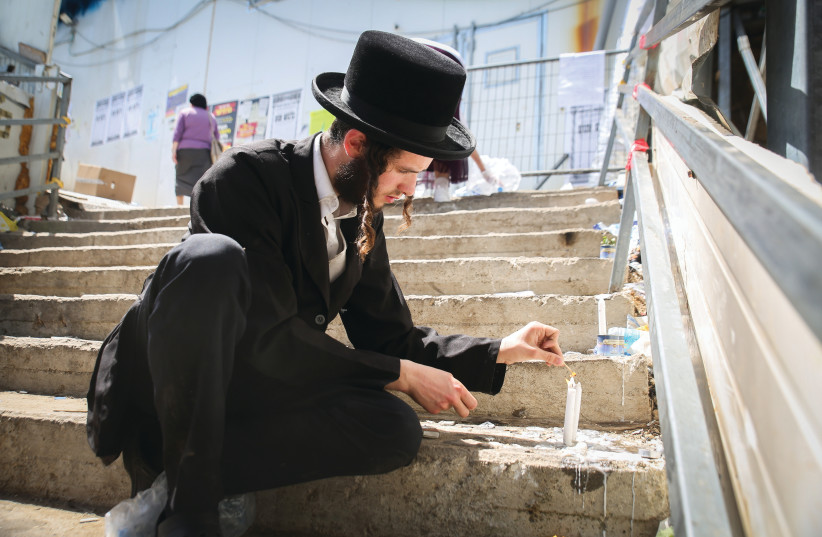 A VISITOR lights a candle at the site where 45 victims were killed in a stampede last week at Mount Meron. (photo credit: DAVID COHEN/FLASH 90)