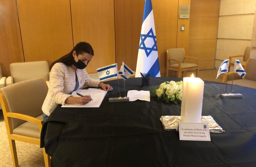 Ambassador of Thailand writing in the book of condolences in the memory of the victims of the Mt.Meron disaster   (photo credit: FOREIGN MINISTRY)