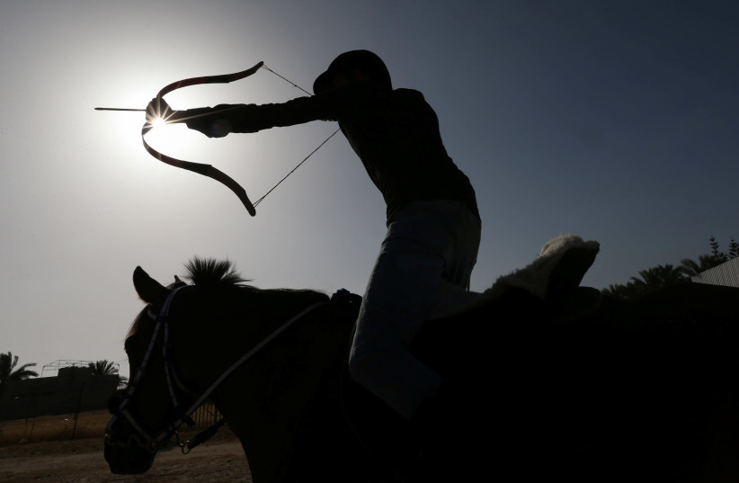 A young Palestinian rider shoots an arrow at a target during a horseback archery training session in Zawayda in the central Gaza Strip April 28, 2021. Picture taken April 28, 2021. (photo credit: IBRAHEEM ABU MUSTAFA / REUTERS)
