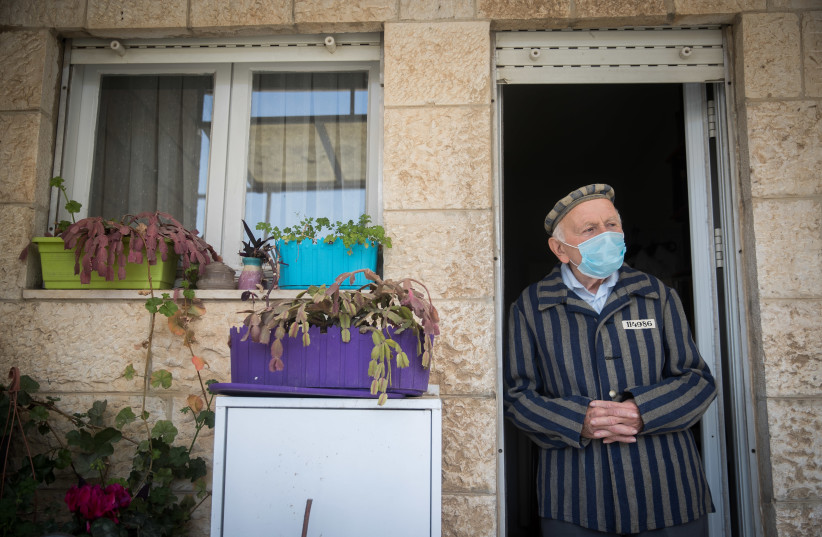 Joseph Kleinman, a 90-year-old holocaust survivor who survived Auschwitz and Dachau Nazi death camp wearing a face mask as he stands at his porch in Jerusalem, during the Holocaust Remembrance Day, April 21, 2020.  (photo credit: YONATAN SINDEL/FLASH 90)