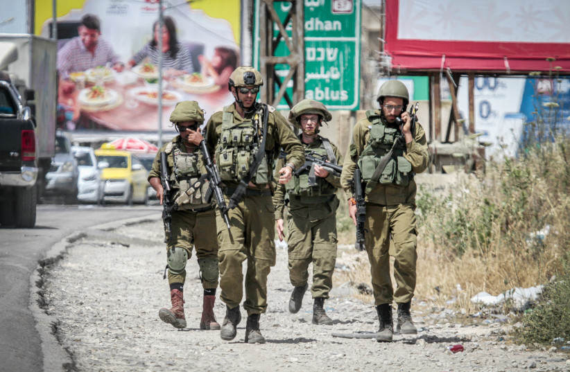 Israeli soldiers guard at the Hawara checkpoint, outside the West Bank city of Nablus, May 4, 2021 (photo credit: NASSER ISHTAYEH/FLASH90)