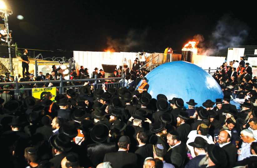 PEOPLE CELEBRATE the lighting of a bonfire  on Mount Meron during Lag Ba'omer last month. (photo credit: DAVID COHEN/FLASH 90)
