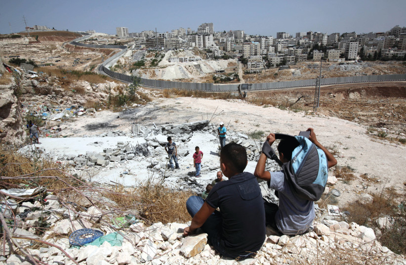 LOOKING ON at the remains of a demolished house, built without authorization, in Isawiya.  (photo credit: YOSSI ZAMIR/FLASH90)