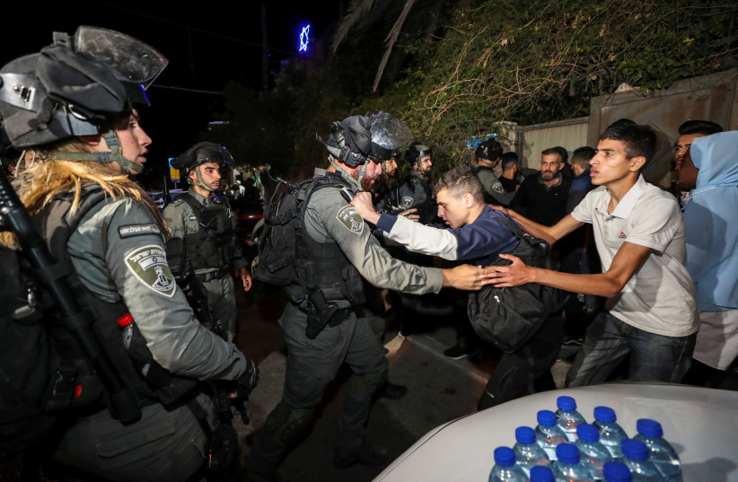 An Israeli border policeman scuffles with a Palestinian protester during clashes amid ongoing tension ahead of an upcoming court hearing in an Israeli-Palestinian land-ownership dispute in the Sheikh Jarrah neighbourhood of East Jerusalem May 3, 2021. (photo credit: REUTERS/AMMAR AWAD)