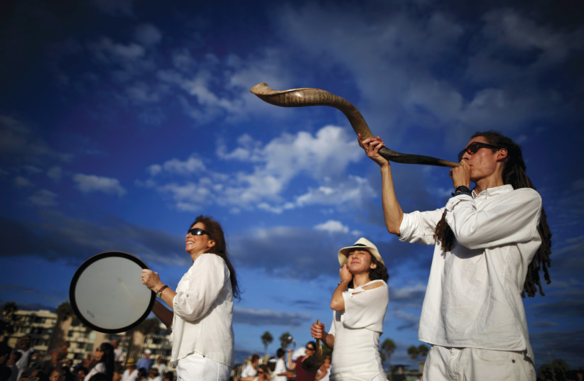 ARED STEIN blows a shofar as Rabbi Naomi Levy plays a drum at the Nashuva Spiritual Community Jewish New Year celebration in LA, 2015 (photo credit: LUCY NICHOLSON / REUTERS)