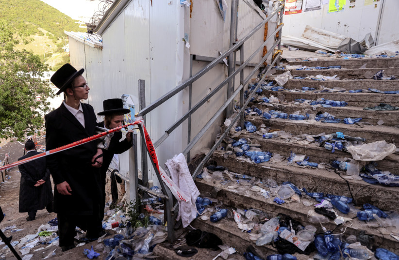 Ultra-Orthodox Jews look at stairs with waste on it in Mount Meron, northern Israel, where fatalities were reported among the thousands of ultra-Orthodox Jews gathered at the tomb of a 2nd-century sage for annual commemorations that include all-night prayer and dance, April 30, 2021. (photo credit: RONEN ZVULUN/REUTERS)