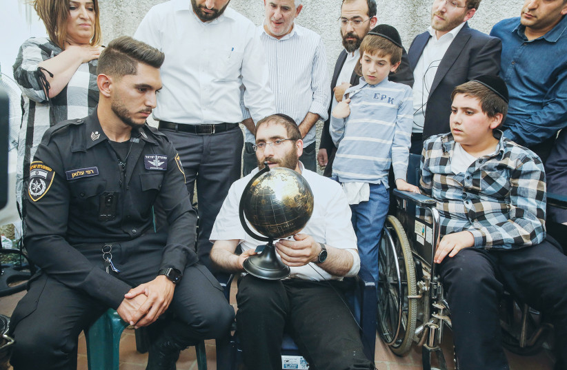 Rabbi Avigdor HAYUT and his son Shmuel meet the Bedouin police officer, Rami Alwan, who helped save them at Mount Meron. The family was sitting shiva for Yedidyia, 13, who died in the disaster. (photo credit: FLASH90)