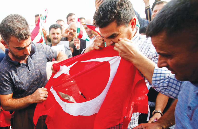 IRAQI KURDS tear the Turkish flag during a demonstration against Turkey's incursion in Syria, outside the UN building in Erbil. (photo credit: AZAD LASHKARI / REUTERS)