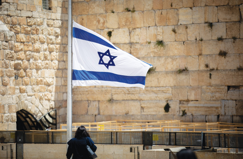 A FLAG at the Western Wall is lowered to half-mast as a mark of mourning for the Mount Meron victims, earlier this week.  (photo credit: YONATAN SINDEL/FLASH90)