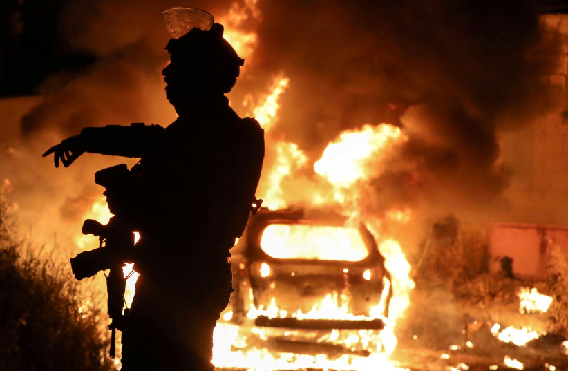 An Israeli policeman gestures as a car belonging to Jewish residents burns amid tension over the possible eviction of several Palestinian families from homes on land claimed by Jews in the Sheikh Jarrah neighborhood in east Jerusalem, May 6, 2021 (photo credit: REUTERS/AMMAR AWAD)