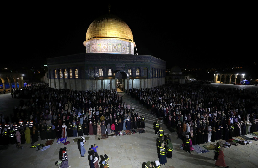 Palestinians pray in front of the Dome of the Rock on Laylat al-Qadr during the holy month of Ramadan, at the compound that houses Al-Aqsa Mosque, known to Muslims as Noble Sanctuary and to Jews as Temple Mount, in Jerusalem's Old City, May 8, 2021. (credit: AMMAR AWAD/REUTERS)