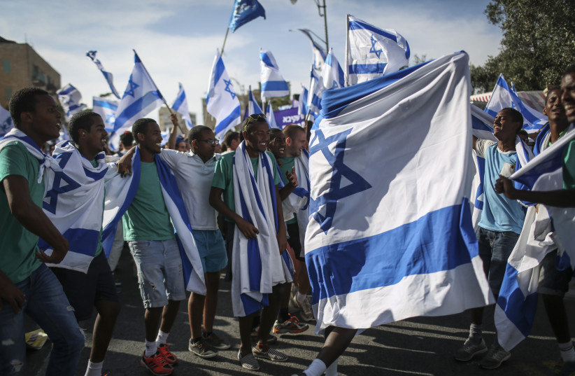 Groups of Jewish youth movements wave Israeli flags as they celebrate Jerusalem Day by the Great Synagogue, on King George Street, before taking part in the parade to the Old City. Jerusalem Day celebrates the 47th anniversary of its capture of Arab East Jerusalem in the Six Day War of 1967.  (photo credit: HADAS PARUSH/FLASH90)