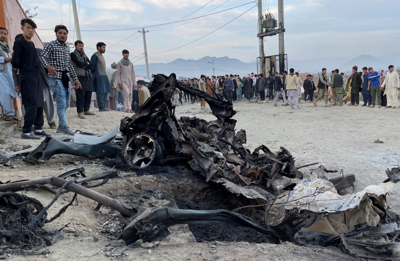 People stand at the site of a blast in Kabul, Afghanistan May 8, 2021. (photo credit: REUTERS/STRINGER)