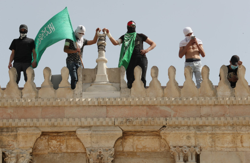 A Palestinian holds a Hamas flag as he stands next to others atop a walk of the al-Aqsa mosque following clashes with Israeli police at the compound that houses al-Aqsa Mosque, known to Muslims as Noble Sanctuary and to Jews as Temple Mount, in Jerusalem's Old City May 10, 2021. (photo credit: AMMAR AWAD/REUTERS)