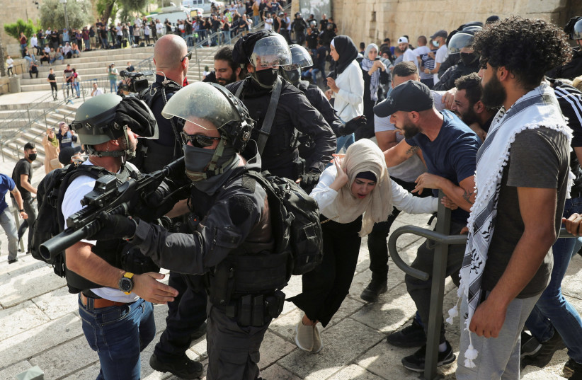 A Palestinian woman reacts during scuffles with Israeli security force members amid Israeli-Palestinian tension as Israel marks Jerusalem Day, near Damascus Gate just outside Jerusalem's Old City May 10, 2021. (photo credit: RONEN ZVULUN/REUTERS)