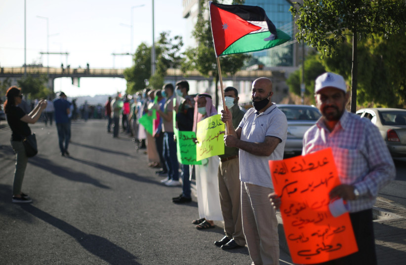 Protesters hold placards and Jordanian national flags as they take a part in a human chain during a sit-in against the annexation of parts of the West Bank by Israel, in Amman, Jordan, June 27, 2020. (photo credit: REUTERS/MUHAMMAD HAMED)