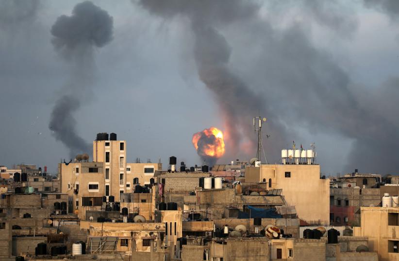 Flames and smoke rise during Israeli air strikes amid a flare-up of Israel-Palestinian violence, in the southern Gaza Strip May 11, 2021 (photo credit: IBRAHEEM ABU MUSTAFA / REUTERS)